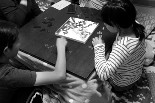 いっしょにボードゲームをするゲストと娘たち
