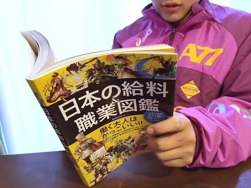 「日本の給料&職業図鑑」を読む小学生