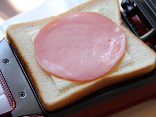 ハムとチーズをパンに挟む