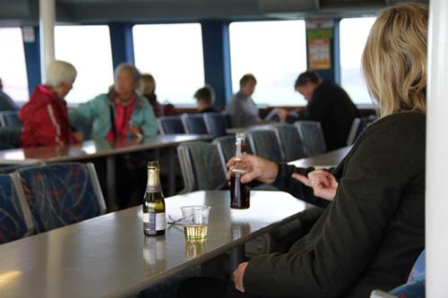 ワイヘキ島へ向かうフェリーの中でワインを飲む乗客