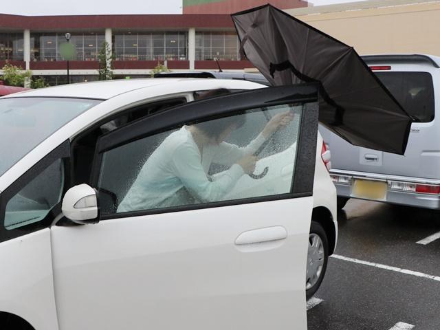 逆さに開く二重傘を閉じながら車に乗る